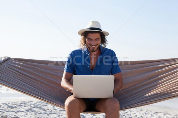 Mosolyog férfi laptopot használ ül függőágy tengerpart Stock fotó © wavebreak_media
