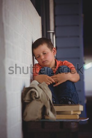 Sad boy sitting on bench by wall in corridor Stock photo © wavebreak_media