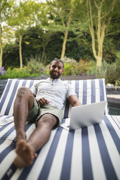 Smiling man using laptop while relaxing on lounge chair at porch Stock photo © wavebreak_media