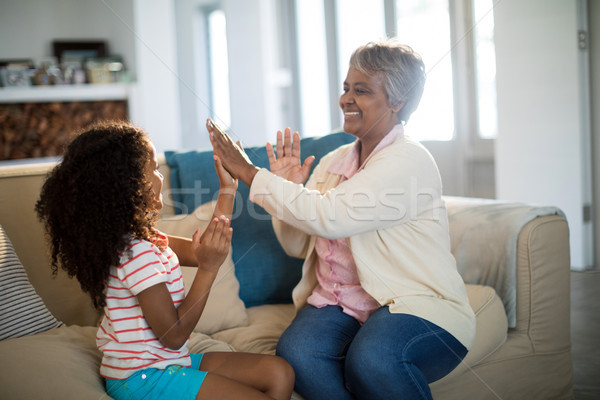Granddaughter and grandmother playing clapping games on sofa in living room Stock photo © wavebreak_media