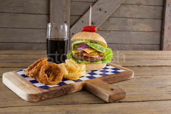 Stock photo: Hamburger, onion ring and french fries with cold drink on chopping board