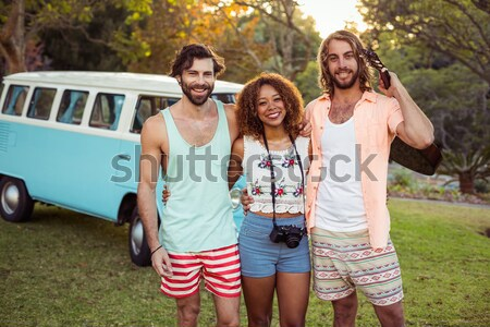 Portrait of happy woman holding beer bottle with friends in background Stock photo © wavebreak_media