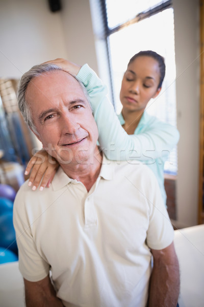 Stock photo: Portrait of senior male patient receiving neck massage from female therapist