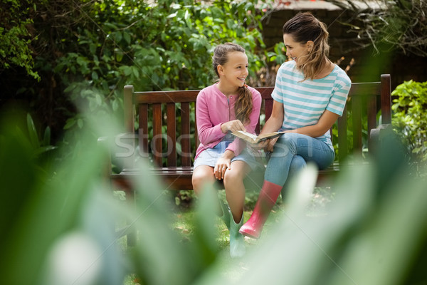 Happy mother and daughter looking at each other while sitting with novel on bench Stock photo © wavebreak_media