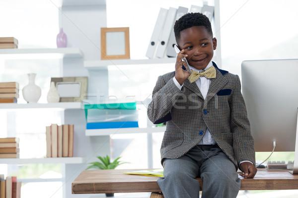 Boy imitating as businessman talking on smart phone Stock photo © wavebreak_media