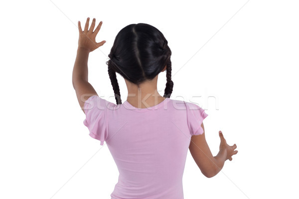 Stock photo: Girl pretending to touch an invisible screen against white background