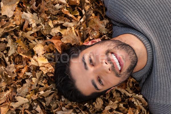 Overhead of man lying on autumn leaves Stock photo © wavebreak_media