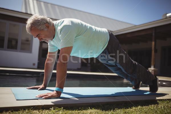 Senior man doing push-up near swimming pool Stock photo © wavebreak_media