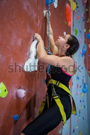 Vastbesloten tienermeisje oefenen rotsklimmen fitness studio Stockfoto © wavebreak_media