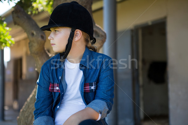 Girl sitting on tree trunk near stable Stock photo © wavebreak_media