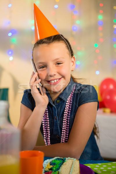 Girl talking on mobile phone during birthday party Stock photo © wavebreak_media