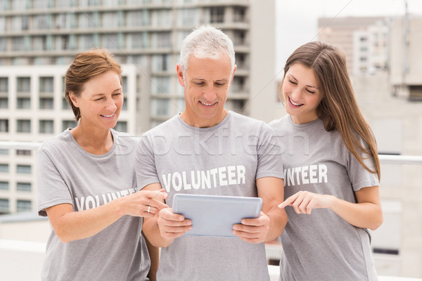 Smiling volunteers using tablet together Stock photo © wavebreak_media