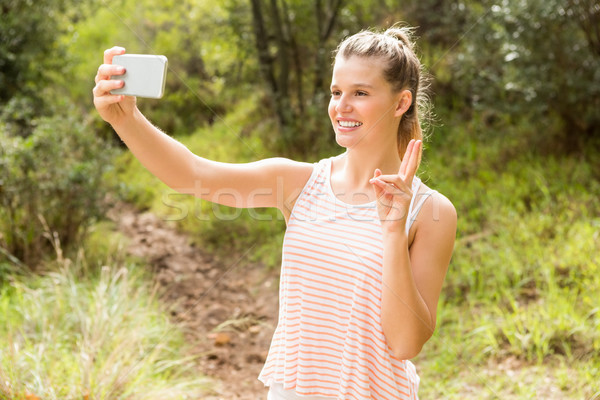 Pretty blonde showing peace sign and taking selfies Stock photo © wavebreak_media