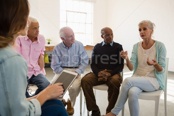 Woman gesturing while sitting with friends and instructor during discussion Stock photo © wavebreak_media