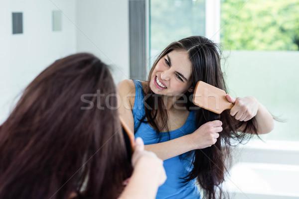 Unsmiling brunette combing Stock photo © wavebreak_media