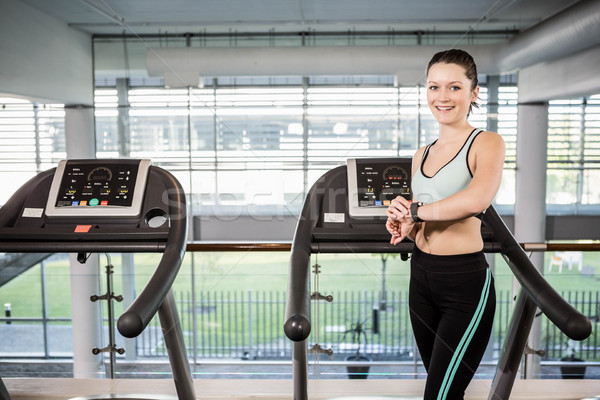 Smiling woman on treadmill using smart watch Stock photo © wavebreak_media