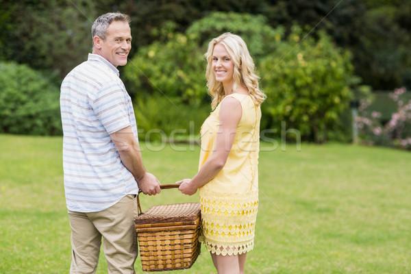 Happy couple holding picnic basket Stock photo © wavebreak_media
