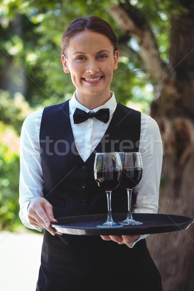 Sorridente garçonete bandeja óculos vinho tinto Foto stock © wavebreak_media