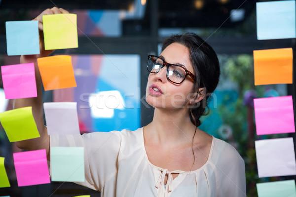 Empresária escrita nota pegajosa escritório mulher óculos Foto stock © wavebreak_media