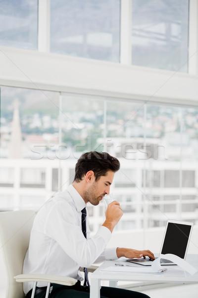 Affaires utilisant un ordinateur portable prendre des notes bureau homme stylo Photo stock © wavebreak_media