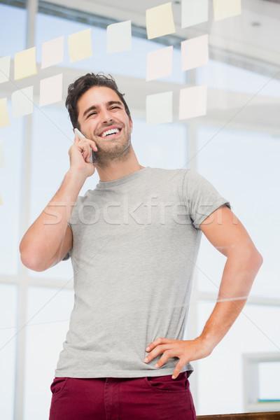Man talking on phone with hand on hip Stock photo © wavebreak_media