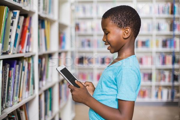 Schoolboy using digital tablet in library Stock photo © wavebreak_media