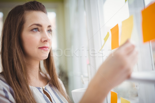 Young businesswoman looking at adhesive notes on window in creat Stock photo © wavebreak_media
