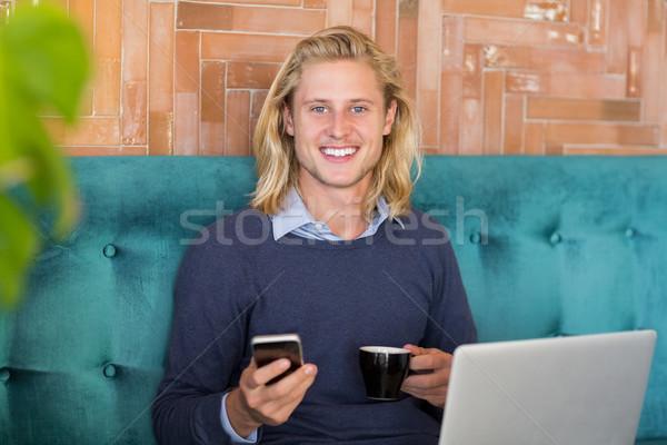 улыбаясь человека мобильного телефона Кубок кофе ресторан Сток-фото © wavebreak_media