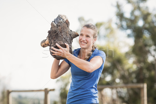 Smiling woman carrying heavy wooden logs during obstacle course Stock photo © wavebreak_media