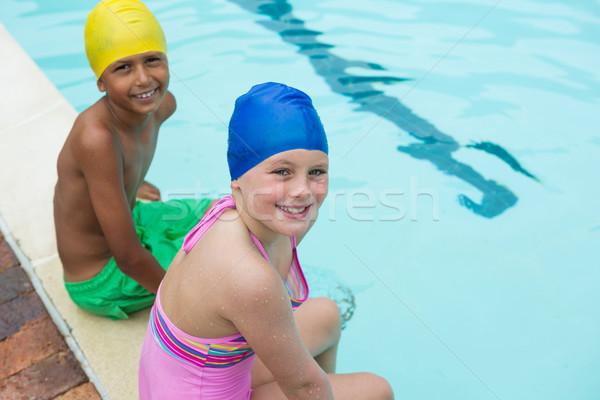 Smiling kids sitting near poolside Stock photo © wavebreak_media
