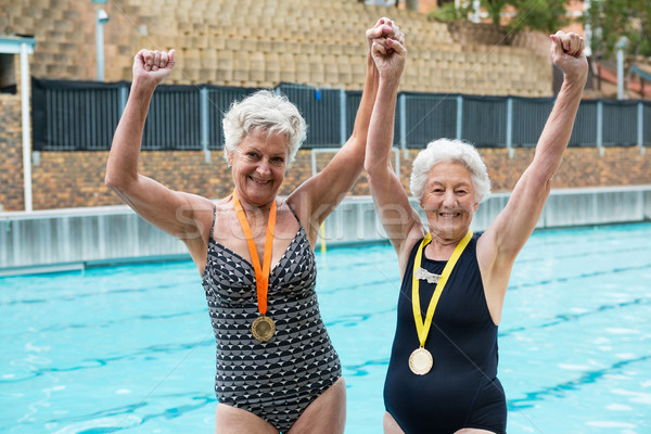 Excited senior women with gold medals standing at poolside Stock photo © wavebreak_media