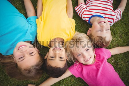 Cute pupils lying on grass smiling Stock photo © wavebreak_media