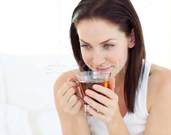 Zachwycony kobieta pitnej herbaty bed twarz Zdjęcia stock © wavebreak_media