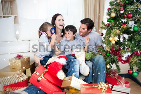 Happy family at Christmas time holding lots of presents Stock photo © wavebreak_media
