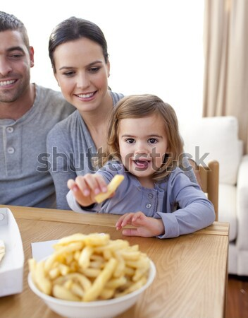 Little girl eating fries and pizza at home Stock photo © wavebreak_media
