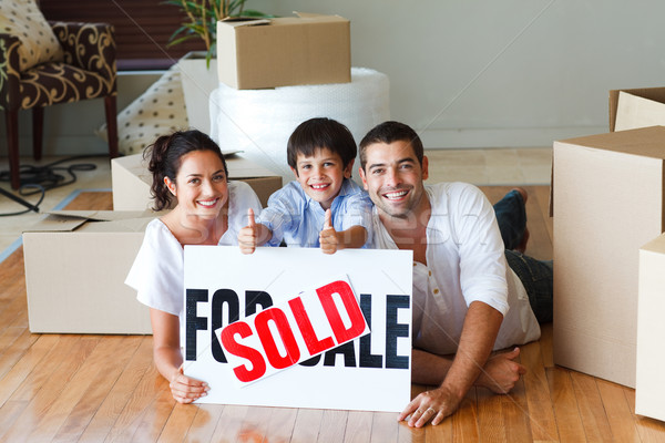 Stock photo: Happy family lying on the floor after buying house