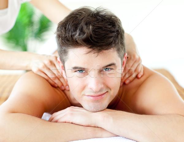 Handsome smiling man enjoying a back massage in a spa center Stock photo © wavebreak_media