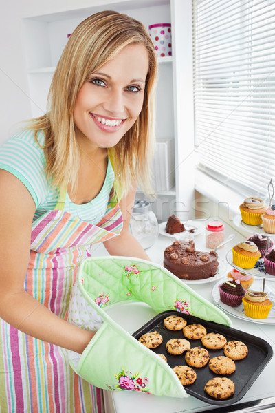 Stock photo: Smiling woman holding cookies in the kitchen at home