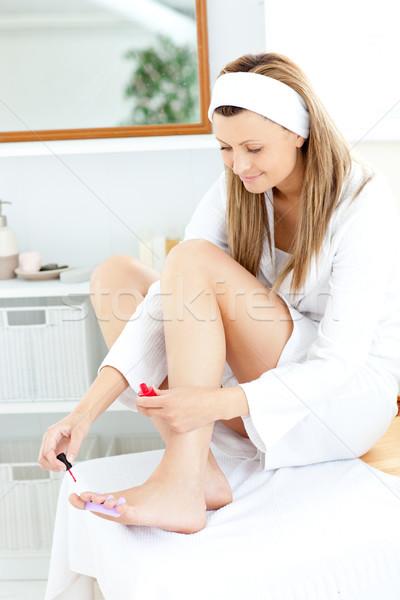 Happy young woman varnishing her toenails in the bathroom at home Stock photo © wavebreak_media