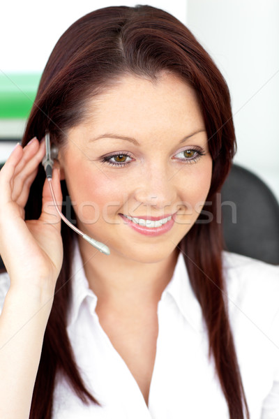 Positive young businesswoman sitting at her desk and wearing earpiece in her office Stock photo © wavebreak_media