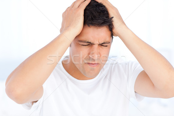 Man suffering from a migraine on waking sitting in his bedroom Stock photo © wavebreak_media