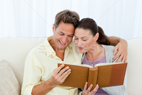Attentive man and woman looking at a photo album on the sofa in the living room Stock photo © wavebreak_media