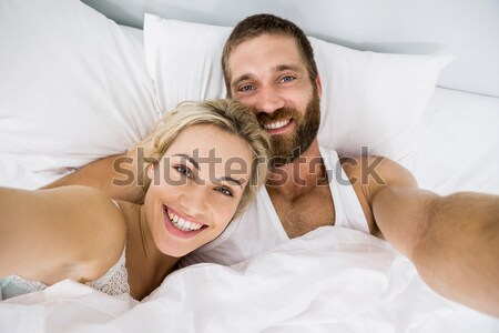 Cute lovers looking at the camera on their bed Stock photo © wavebreak_media