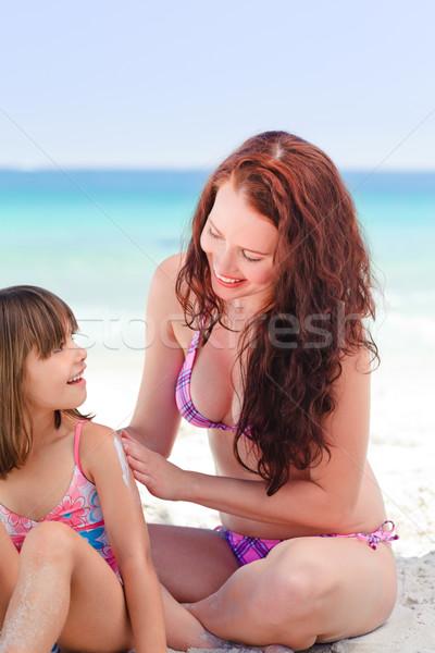 Mother applying sun cream on her daughter's back Stock photo © wavebreak_media