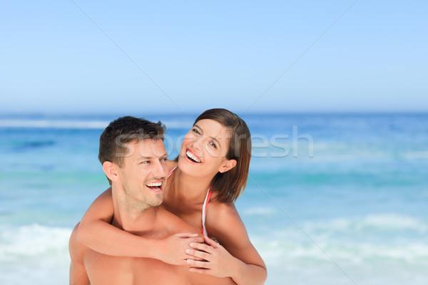 Homem bonito esposa piggyback praia água sorrir Foto stock © wavebreak_media