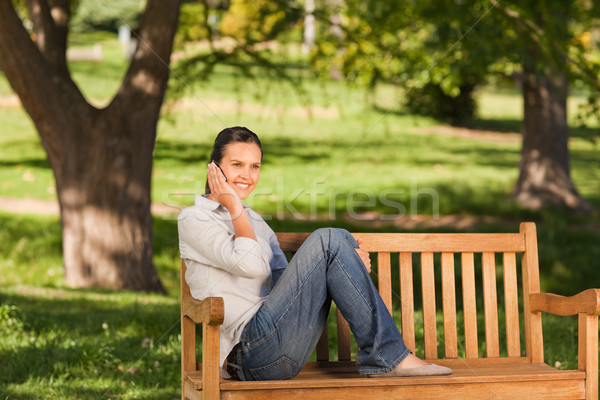 Young beautiful woman phoning on the bench Stock photo © wavebreak_media