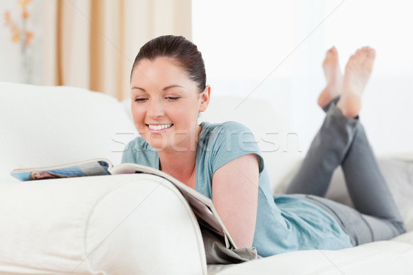 Charming woman reading a magazine while lying on a sofa in the living room Stock photo © wavebreak_media