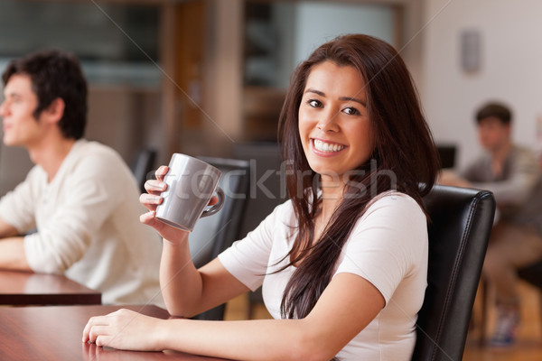 Cute woman having a coffee while looking at the camera Stock photo © wavebreak_media