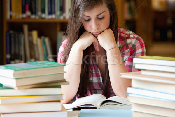 Studious woman surrounded by books in a library Stock photo © wavebreak_media
