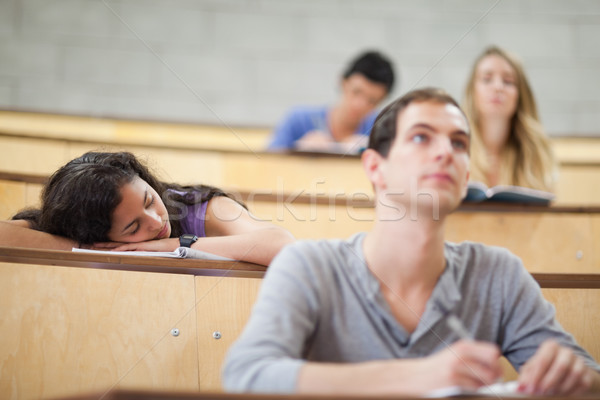 Students listening a lecturer while their classmate is sleeping in an amphitheater Stock photo © wavebreak_media